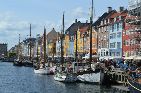 Colourful houses sat on the waterfront of a city in Denmark. There are boats on the water in front of the houses.